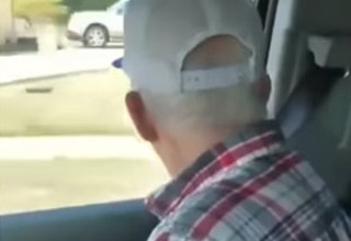 an elderly white man with a red white and blue plaid shirt on and a white ball cap looking out a car window