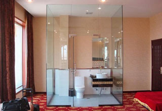 Bathroom made of glass in the middle of a hotel room