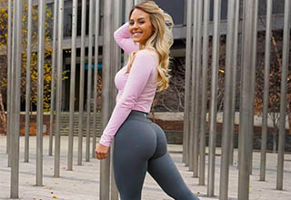 A hot girl wearing yoga pants and a pink shirt.