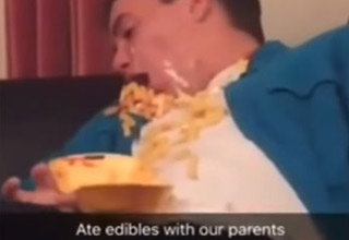 a guy wearing a blue shirt covered in nachos and cheese laughing high on edibles