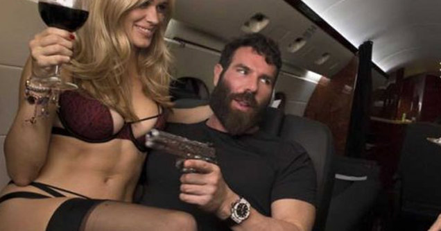 dan bilzerian in a private jet holding a gun and a hot model in a bikini is on his lap with a glass of wine