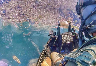 a navy fighter pilot looking down a city from very high up in the sky