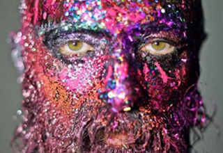 a mans face covered in pink and fluorescent paint and glitter