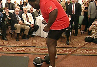 olympian and wwe wrestler mark henry is in a room full of people about to life a 172 pound thomas inch dumbbell