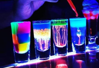 5 shot glasses on a bar filled with neon and fluorescent colored liquids