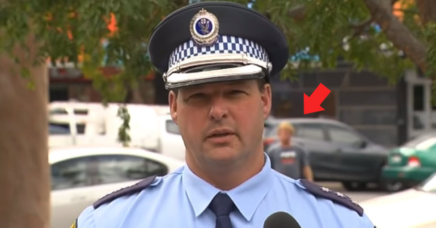 an australian police officer giving a press interview and a drunk man behind him walking and a red arrow pointing to him
