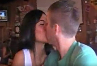 a brunette hooters waitress getting a surprise kiss from a customer after losing a bet.