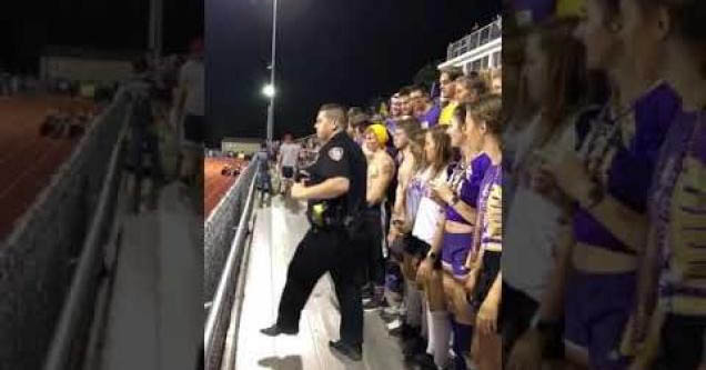 A cop dancing with a team.
