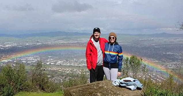 Two people on a hike taking a picture with a rainbow.