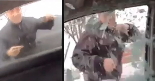 A guy punches the glass out of a car.A guy punches the glass out of a car.