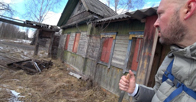a man holding a knife in front of an old abandoned building in the chernobyl zone