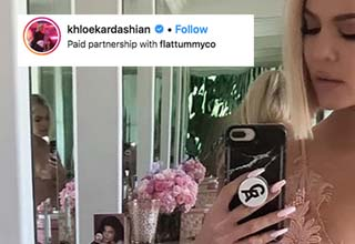 khole kardashian taking a photo in a mirror with an instagram comment on top