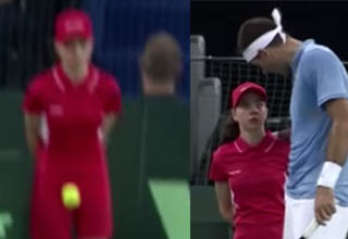 Ball girl getting hit with ball during tennis match. Del Potro tennis player helping ball girl.