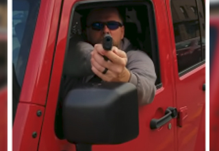 a man in a red jeep suv holding a gun at the camera man