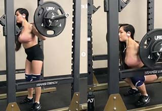 a lady lifting weights in a gym and squatting
