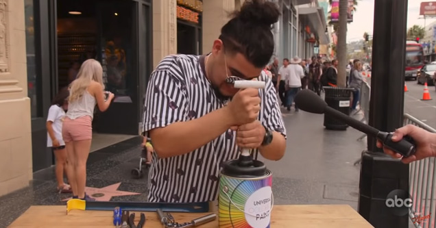 a millenial man with a manbun trying to open a can of paint with a plunger