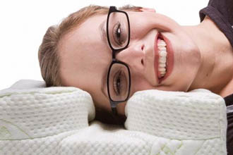 A picture of a woman with glasses laying down.