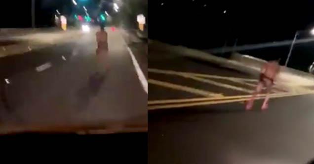 Half naked man running in the street.