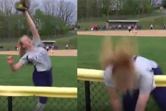 A girl falling over a fence while playing softball.
