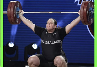 8d9a2bf31 joe rogan looking a a photo of a trans female weightlifter breaking a world  record
