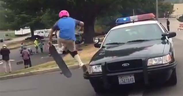 kid jumping over a police cruiser on his skateboard