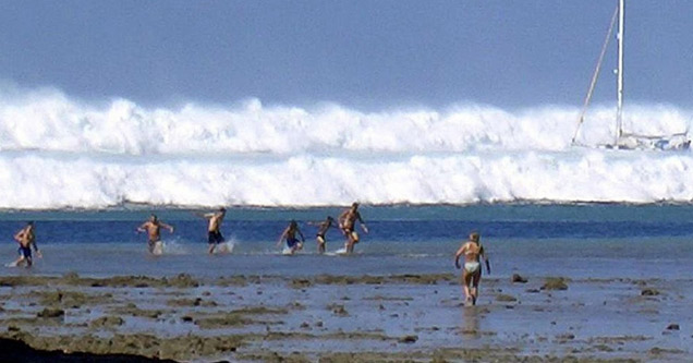 a photo of people running away from the indonesia tsunami on the beach