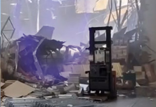a photo from inside of a warehouse after a military jet crashed into it