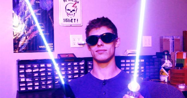 a dude holding two lasers and wearing goggles