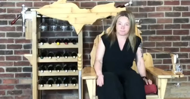 white woman sitting in a wooden chair with a built in wine bar