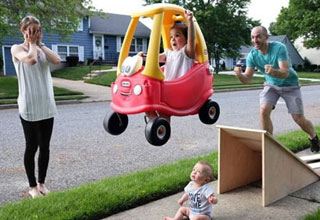 a family photo of a kid jumping his baby brother in a toy car off a ramp and mom has her hands over here eyes in fear