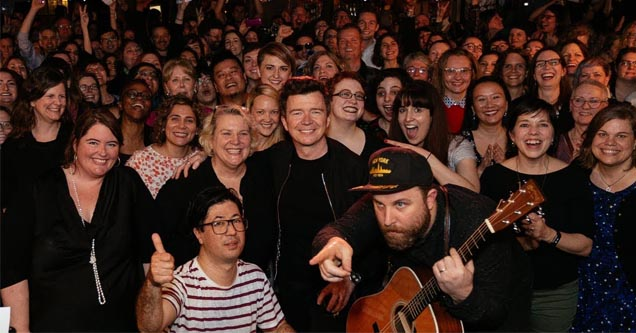 rick astley with a big crowd of people and a man with a guitar