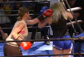 a woman in a sleeeless tan shirt and brown pants is boxing another woman in tight blue booty shorts and a tank top