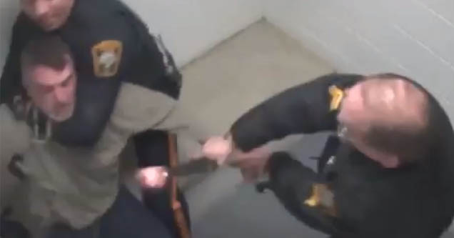a police officer aiming a gun at a prisoner in a cell