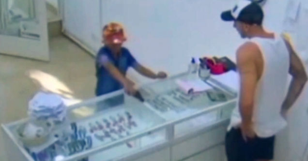 a young boy in a blue shirt holding a gun and a store owner in a white tank top behind the counter