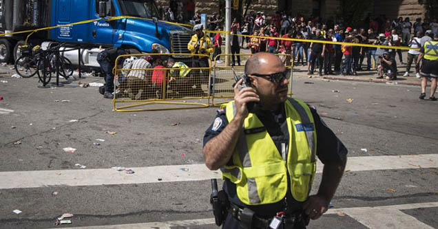 A police officer talks on a phone as first responders attend to an injured person during the Toronto Raptors championship parade.