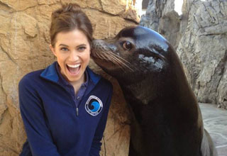 a seal kissing a smiling woman