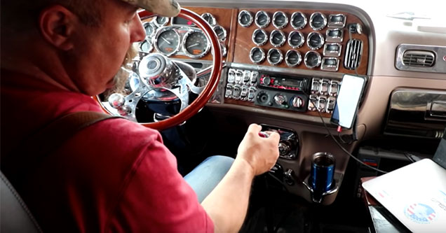Trucker sitting inside his cab shows us how to shift his 18 gear rig