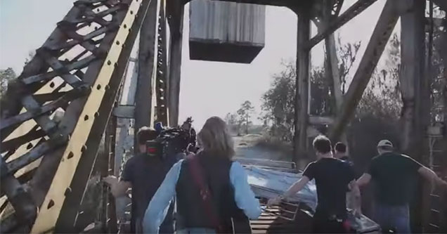 film crew get caught on a bridge as a train comes down the tracks