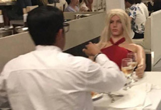 a man in a white shirt at a restaurant sitting across from a sex doll