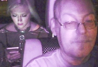 a dashcam image of an uber driver with a girl on her phone in the back