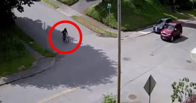 a cyclist circled in red speeding down a hill where an SUV awaits