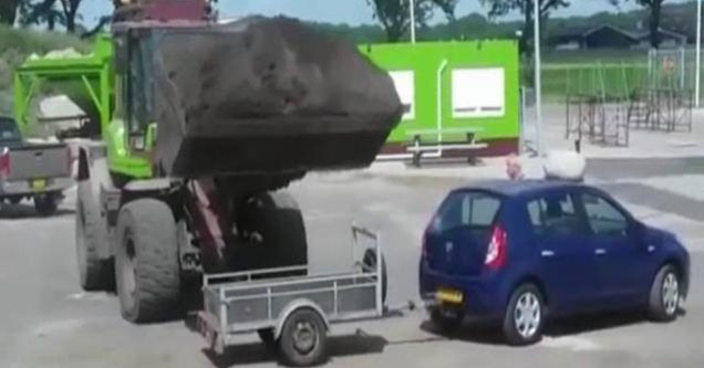 loader filled with sand ready to dump on a small car with a trailer