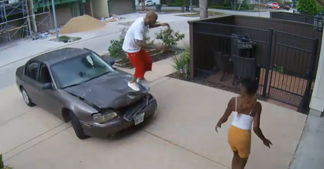 a man in a white shirt and red shorts is jumping on his cars hood to try and straighten it out
