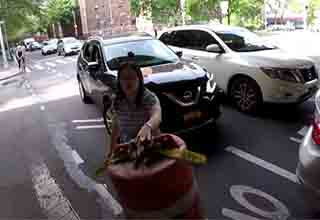 a lady holding a cone up toward the camera man in the bike lane