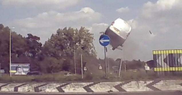 a white minivan way up in the air after hitting a roundabout