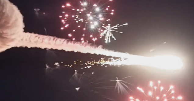 an airplane flying and shooting off fireworks and laser beams