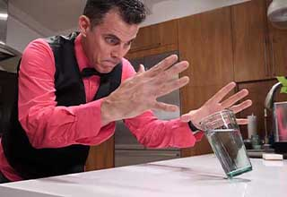 Steve-O balances a pint glass on a dime for a bar trick