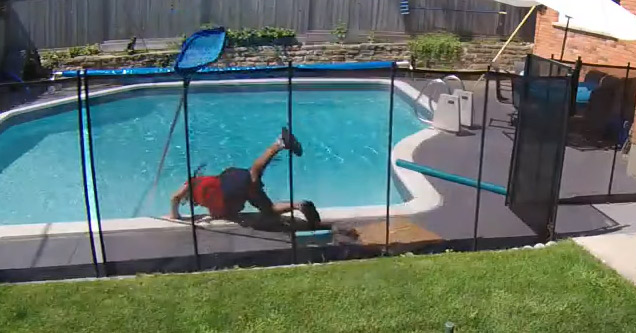 a pool maintenance worker in red shirt and blue shorts falling into pool
