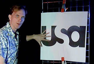 a dude standing in front of the usa television logo