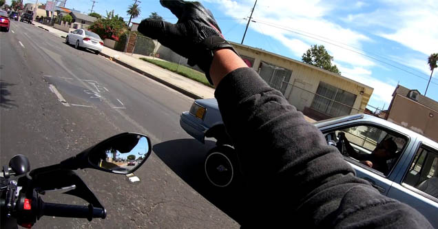 a motorcycle waving at a car on the road in compton